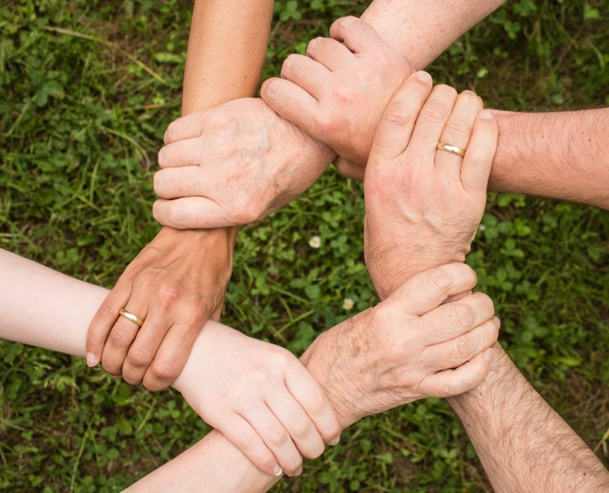 six hands holding each other by the wrist in a circle