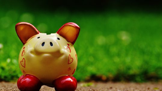 Yellow and red ceramic piggy bank on the ground in front of grass