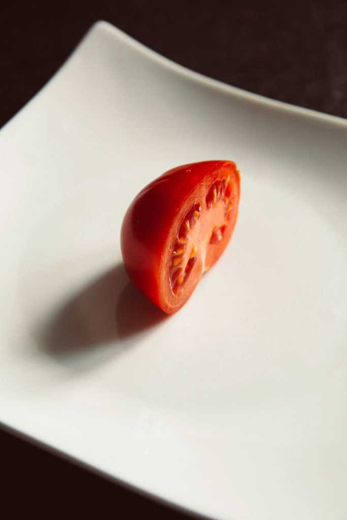 A white ceramic plate with half of a tomato on it